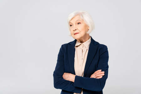 Senior woman in jacket standing with crossed arms isolated on gray