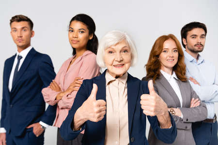 Smiling businesswoman showing like near multicultural businesspeople on blurred background isolated on gray