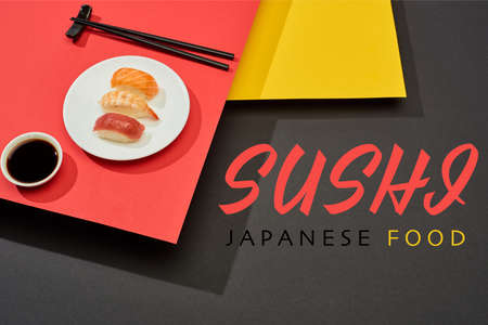 fresh nigiri with salmon, shrimp and tuna near soy sauce, chopsticks and sushi japanese food lettering on red, yellow and black surface