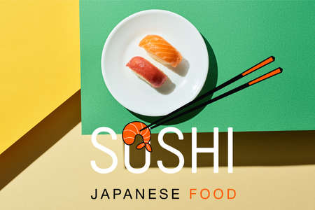 top view of fresh nigiri with salmon and tuna near sushi, japanese food lettering on green and yellow surface