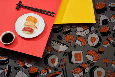 fresh nigiri with salmon, shrimp and tuna near soy sauce, chopsticks and sushi illustration on red and yellow surface