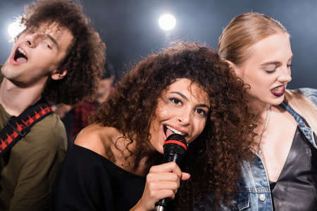 Happy rock band vocalist with microphone singing near musicians with backlit on blurred background Foto de archivo