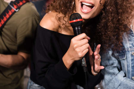 Cropped view of curly female vocalist with microphone singing near rock band musicians on blurred background Stock Photo