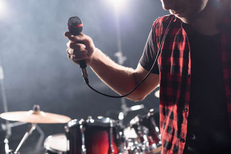 Cropped view of vocalist with microphone with blurred drum kit on background