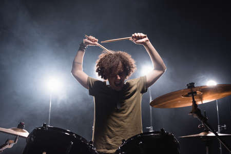 Curly musician shouting, while holding drumsticks and sitting at drum kit with backlit on background