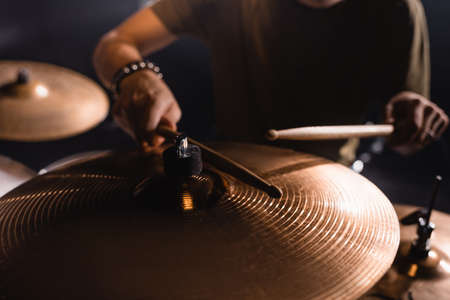 Cropped view of metal cymbals with blurred musician with drumsticks on background Stock Photo