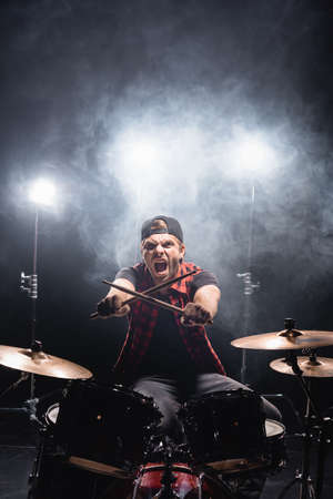 Screaming drummer with crossed drumsticks looking at camera, while sitting at drum kit with smoke and backlit on background