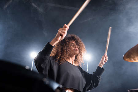 Rock band musician with drumsticks playing on cymbal on blurred foreground Stock Photo