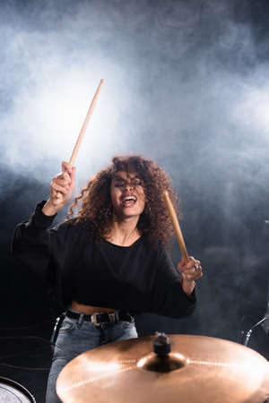 Female drummer with closed eyes shouting, while playing on drum plate with smoke on black background Stock Photo