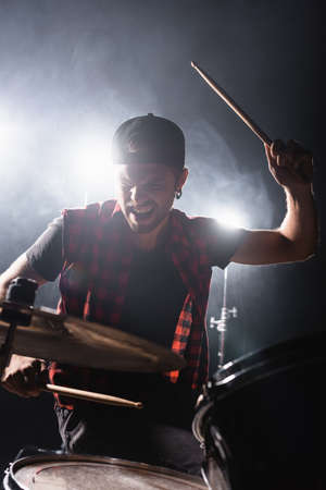 Rock band drummer holding drumstick and playing drums with back light and smoke on background