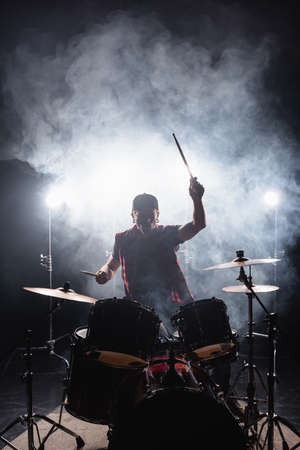 Man playing drums while sitting at drum kit with backlit and smoke on background Stock Photo