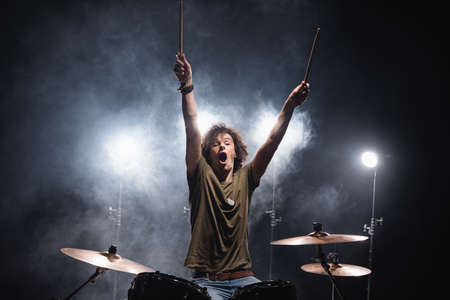 Shouting musician with hands in air sitting at drum kit with smoke and backlit on background