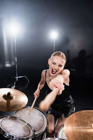 High angle view of excited blonde pointing with drumstick while sitting at drum kit with backlit on blurred foreground Stock Photo