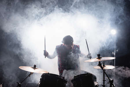 Musician with drumsticks playing while sitting at drum kit with smoke and backlit on background