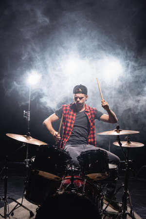 Serious musician with drumsticks playing drums with smoke and backlit on black