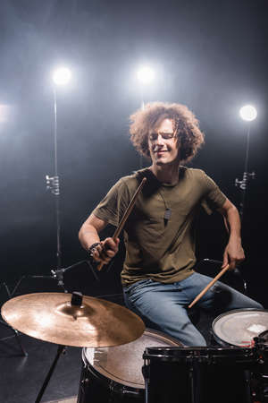 Curly musician playing while sitting at drum kit with drumsticks with back light on background