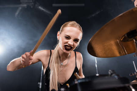Blonde woman with drumstick winking and playing drum plate on blurred foreground