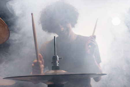 Smiling curly drummer with drumsticks playing drums in smoke
