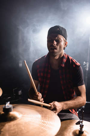 Rock band musician holding drumsticks and playing on drums with smoke on black Stock Photo