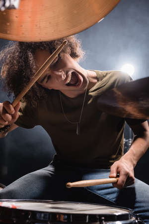 Curly musician shouting while playing drum with drumsticks on blurred foreground