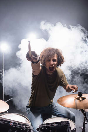 Curly drummer pointing with drumstick while shouting and sitting at drum kit with smoke on background
