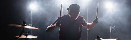 Rock band member with drumsticks playing drums with backlit and smoke on background, banner