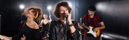 KYIV, UKRAINE - AUGUST 25, 2020: Curly vocalist with closed eyes singing in microphone near guitarists with backlit and female drummer on background, banner Editorial