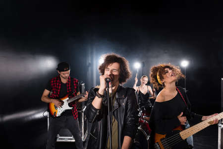 KYIV, UKRAINE - AUGUST 25, 2020: Curly vocalist with closed eyes singing in microphone near guitarists with backlit and female drummer on background