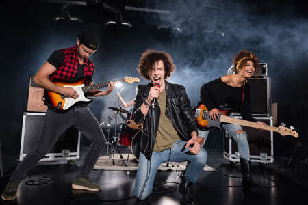 KYIV, UKRAINE - AUGUST 25, 2020: Curly vocalist shouting in microphone while sitting on knee near guitarists during rock band performance with backlit on black