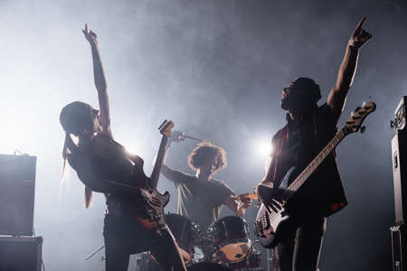KYIV, UKRAINE - AUGUST 25, 2020: Rock band guitarists with hands in air singing with smoke and drummer on background