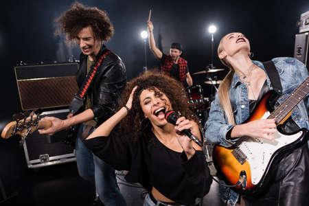 KYIV, UKRAINE - AUGUST 25, 2020: Female singer of rock band with microphone singing near guitarists with blurred drummer on background