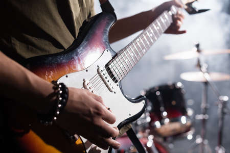 KYIV, UKRAINE - AUGUST 25, 2020: Cropped view of rock band guitarist holding guitar pick near strings on blurred background Editorial