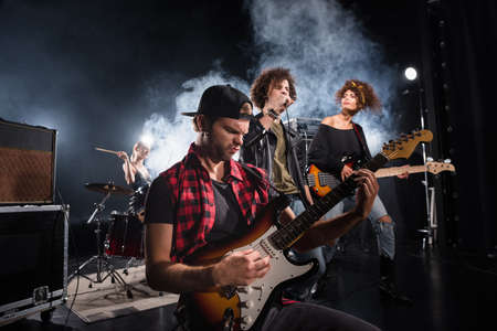 KYIV, UKRAINE - AUGUST 25, 2020: Rock band musician playing bass guitar sitting near curly vocalist and guitarist with smoke and female drummer on background