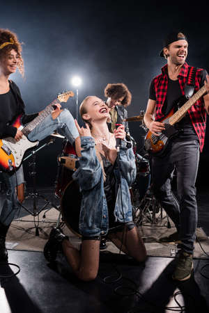KYIV, UKRAINE - AUGUST 25, 2020: woman with microphone showing rock sign while sitting on knees near musicians with backlit on black background