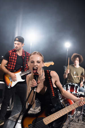 KYIV, UKRAINE - AUGUST 25, 2020: Female vocalist of rock band with electric guitar screaming in microphone with backlit and blurred musicians on background