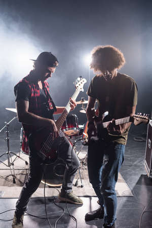 KYIV, UKRAINE - AUGUST 25, 2020: Rock band musicians playing electric guitars near drum kit with back light on background