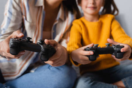 KYIV, UKRAINE - SEPTEMBER 15, 2020: cropped view of mother and daughter gaming with joysticks on blurred background, banner