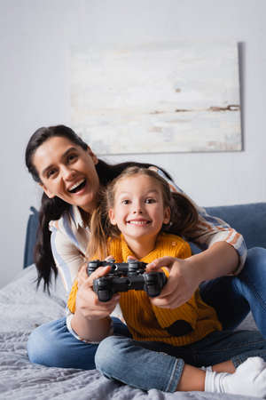 KYIV, UKRAINE - SEPTEMBER 15, 2020: excited mother and daughter playing video game in bedroom Stok Fotoğraf