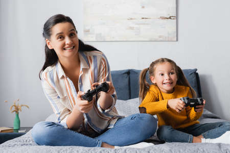 KYIV, UKRAINE - SEPTEMBER 15, 2020: happy girl with mother gaming with joysticks in bedroom