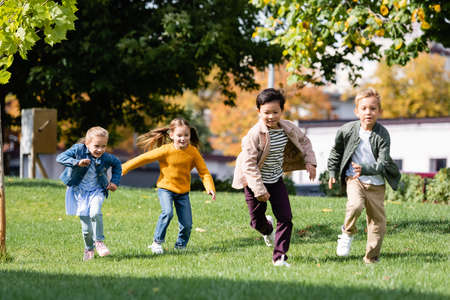Smiling multiethnic children running on grass in park Banque d'images