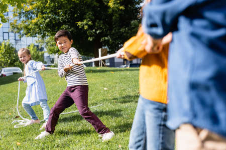Asian boy playing tug of war with friends on blurred foreground on grass in park Stockfoto