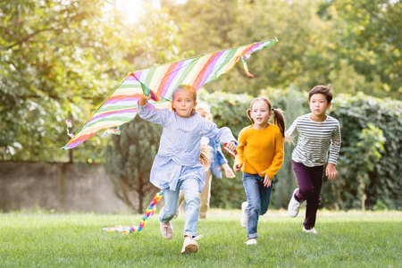 Girl holding flying kite while running near multiethnic friends in park Archivio Fotografico