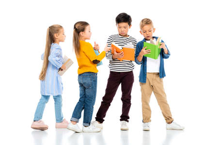 Multiethnic kids holding colorful books on white background