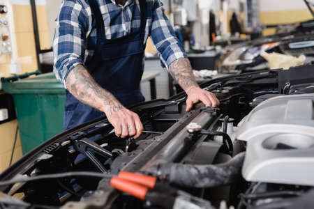 cropped view of mechanic checking car engine compartment in workshop on blurred foreground