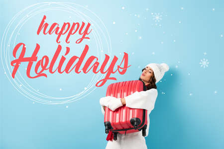 young woman in winter outfit carrying heavy suitcase near happy holidays lettering on blue