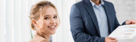 Happy female executive looking at camera with blurred co-worker on background, banner Stock Photo