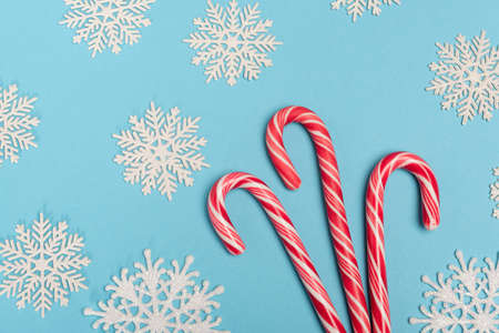 top view of candy cane and snowflakes on blue background