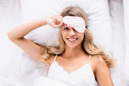 Top view of young woman in blindfold smiling at camera on bed