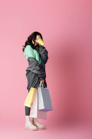 smiling brunette young woman in casual winter outfit with shopping bags and coffee to go on pink background Stock fotó