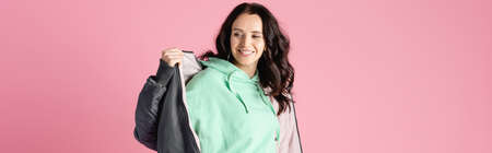 smiling brunette young woman in casual winter outfit posing on pink background, banner Stock fotó